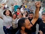 Libanesische Anti-Regierungsprotestler feiern in der Hauptstadt Beirut den Rücktritt von Ministerpräsident Saad Hariri. (Bild: KEYSTONE/AP/BILAL HUSSEIN)