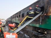 Rettungskräfte suchen nach Überlebenden des Brandes im Zug. (Bild: KEYSTONE/AP/SIDDIQUE BALUCH)