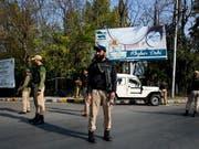 Indische Polizisten stehen an einer Strasse in Srinagar Wache, die zum Regierungsgebäude führt. Dort legte der neue Gouverneur von Jammu und Kaschmir den Amtseid ab. (Bild: KEYSTONE/EPA/FAROOQ KHAN)