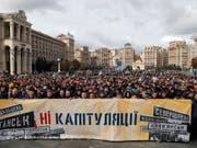 «Nein zur Kapitulation!» steht auf dem Transparent. Tausende Menschen haben am Sonntag in Kiew gegen gegen den Ostukraine-Plan der Regierung demonstriert. (Bild: KEYSTONE/EPA/SERGEY DOLZHENKO)