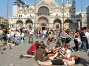 Touristen auf dem Markusplatz in Venedig. Ab Mitte nächsten Jahres müssen Tagestouristen Eintrittsgeld für einen Besuch in der Lagunenstadt bezahlen. (Bild: KEYSTONE/AP/GIGI COSTANTINI)