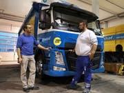 Geschäftsleitungsmitglied Dominic Imhof diskutiert mit Fahrer Marc Streit vor dem E-Lastwagen. (Bild: Martina Eggenberger)