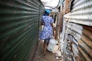 Eine Frau trägt in einem Township in der Nähe von Kapstadt Wasser zu ihrer Unterkunft. Die herrschende Armut breiter Bevölkerungsschichten bleibt für Südafrika auch 25 Jahre nach dem Ende der Apartheid eines der grossen Probleme. (Bild: Nic Bothma/Keystone - 6. November 2019)