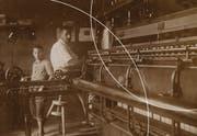 Fotograf unbekannt (ca. 1900-1915). Heimsticker am Pantograph der Handstickmaschine und Knabe an Fädelmaschine im Sticklokal. In Schweizerisches Landesmuseum. (Bild: PD)