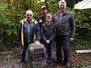 Walter Rohner (links) freut sich über die Neusetzung des Grenzsteins an seinem Grundstück. Dieser wurde auf dem Land von Adrian, Alex und Silvan Steiner in Baar gefunden. (Bild: Sabine Windlin/PD)