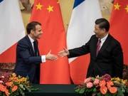 Der französische Präsident Emmanuel Macron (l) und der chinesische Staatschef Xi Jinping warnen in einem gemeinsamen Papier, dass «der Verlust biologischer Vielfalt und der Klimawandel weltweit den Frieden und die Stabilität bedrohen». (Bild: KEYSTONE/EPA AFP POOL/NICOLAS ASFOURI / POOL)