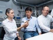 Laura Heyderman und Tian-Yun Huang (Mitte) betrachten ein vergrössertes Modell des Mikroroboters, der an einen Origami-Vogel erinnert. Jizhai Cui (rechts) betrachtet den echten Mikroroboter unter einem Mikroskop. (Bild: Paul Scherrer Institut)