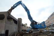 Der blaue Bagger setzt zum Abbruch an: Mit einem Spezialfahrzeug wird der Betonbau Stück für Stück weggetragen. (Bild: Géraldine Bohne)