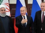 Russlands Präsident Wladimir Putin (Mitte) fordert am Syrien-Gipfel in Sotschi die USA auf, die Truppen rasch aus Syrien abzuziehen. Am Gipfel vereinbarte er mit dem türkischen Staatschef Recep Tayyip Erdogan (rechts) und Irans Präsident Hassan Ruhani, das Vorgehen im Syrien zu koordinieren. (Bild: KEYSTONE/EPA POOL/SERGEI CHIRIKOV / POOL)