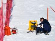 Ein Helfer werkelt in Crans-Montana an einer Zeitmessanlage (Bild: KEYSTONE/ALESSANDRO DELLA VALLE)