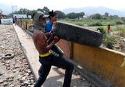 Zivilisten versuchen, auf der Grenzbrücke Simón Bolívar den Weg freizumachen für humanitäre Transporte von Kolumbien nach Venezuela. Bild: Ernesto Guzman/EPA (Cúcuta, 24. Februar 2019)