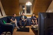 Yannick Keuker, Vincent Moix und Adam Stewart (von links) schauen in ihrer WG gemeinsam Fussball. (Bild: Michel Canonica - 21. Februar 2019)