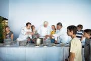 Zuger Schüler kochen im Rahmen des Genuss-Film-Festivals gemeinsam mit den Köchen Peter Bechter (links), Stefan Meier (Mitte) und Edi Hitzberger, nachdem sie sich einen Film zum Thema «Slow Food» im Kino Seehof angeschaut haben. (Bild: Maria Schmid, Zug, 7. Mai 2018)