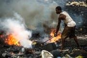 Lodernde Feuer und giftiger Qualm: Die Menschen, die auf Accras Schrotthalde arbeiten, werden nicht alt. (Bild: PD)