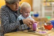 Ein Kleinkind schnitzt mit der Hilfe seiner Grossmutter ein Räbeliechtli für den Räbeliechtliumzug, aufgenommen im Gemeinschaftszentrum Loogarten. (Bild: Gaetan Bally/Keystone (Zürich, 6. November 2014))