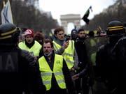 Teilnehmer der «Gelbwesten»-Proteste auf den Champs-Elysées am Samstag. (Bild: KEYSTONE/AP/KAMIL ZIHNIOGLU)