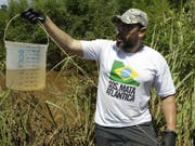 Ein Biologe der Umweltorganisation SOS Mata Atlantica mit einer Wasserprobe aus dem Fluss Paraopeba, dessen Leben durch den Dammbruch zerstört wurde. (Bild: Keystone/AP/ANDRE PENNER)