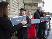 Mitglieder des Komitees reichen am Montag bei der Bundeskanzlei die Unterschriften für die Petition «Hürden abbauen - Behandlung psychischer Krankheiten sicherstellen» ein. (Bild: Keystone/PETER KLAUNZER)