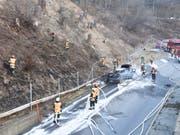 Die Feuerwehrleute mussten nicht nur den Autobrand löschen, sondern auch die Flammen auf der Böschung. (Bild: Kapo GR)
