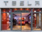 Tesla schliesst doch weniger Läden als angekündigt, erhöht dafür aber die Preise der Fahrzeuge. Im Bild: Tesla-Showroom in Berlin. (Bild: KEYSTONE/EPA/JENS SCHLUETER)