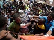 Aus den Trümmern des eingestürzten dreistöckigen Gebäudes in Lagos wird ein Kind geborgen. (AP Photo/Sunday Alamba) (Bild: KEYSTONE/AP/SUNDAY ALAMBA)