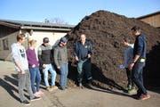 Ruedi Daepp erklärt Lehrlingen aus Zürich, wie sie mit Kompost arbeiten können. Bild: Trudi Krieg