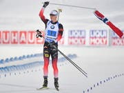 Johannes Thingnes Bö muss zum Schluss nicht spurten, sondern er schwingt Norwegens Fahne. (Bild: KEYSTONE/EPA TT NEWS AGENCY/JESSICA GOW)