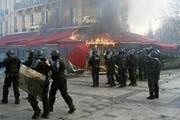 Polizisten sichern ein in Flammen stehendes Restaurant. Bild: Yoan Valat/EPA (Paris, 16. März 2019)