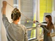 Zwei Schülerinnen der Zürcher Schule für Gestaltung bereiten das Bekleben der Rollläden vor.