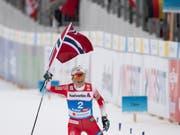 So überlegen, dass sie mit der norwegischen Flagge ins Ziel laufen konnte: Weltmeisterin Therese Johaug (Bild: KEYSTONE/PETER SCHNEIDER)