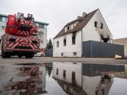 Ein Feuerwehrwagen steht neben einem Haus mit Brandspuren. Bei dem Brand in dem Nürnberger Wohnhaus sind vier Kinder und eine Frau ums Leben gekommen. (Bild: Keystone/DPA/LINO MIRGELER)