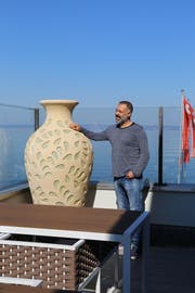 Pächter Zeki Ok zeigt stolz die Aussicht auf dem Balkon im ersten Stock des Seerestaurants. Mannshohe, vasenförmige Lampen sollen bei Dunkelheit für ein gemütliches Ambiente sorgen. (Bild: Martin Rechsteiner)