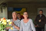 Marianne Burger Studer und ihr Mann Hans-Jörg Studer (links) freuen sich am Wahl-Apéro vor der Turnhalle in Lütisburg. Der unterlegene Werner Scherrer (hinten rechts) klatscht mit. (Bild: Timon Kobelt)