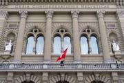 Eine Person installiert die Schweizer Flagge auf dem Balkon vor dem Ständerat beim Bundeshaus. (Bild: Anthony Anex / Keystone, Bern, 12. März 2019)