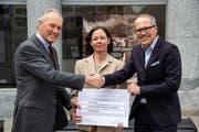 Spendenübergabe vor der Tourist Information (von links): Jan Poëll und Karin Fagetti von Cheira sowie Tourismusdirektor Thomas Kirchhofer. (Bild: PD)