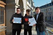 Ozan Avci und Nael Zidan übergeben Gemeindeschreiber Thomas Baumgartner die Unterschriftensammlung. (Bild: PAG)