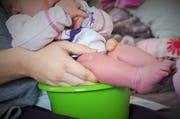 Tamara Beck beim «Abhalten» ihres Babys über einem Töpfchen. (Bild: Tamara Beck/nestwaerme.li)