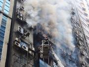 An der Bekämpfung des Brandes in Dhaka beteiligten sich zahlreiche Einheiten der Feuerwehr. Auch die Armee unterstützte den Grosseinsatz. Helikopter warfen Wasser über dem brennenden Büroturm ab. (Bild: KEYSTONE/AP/MAHMUD HOSSAIN OPU)