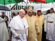Papst Franziskus wird bei seiner Ankunft auf dem Flughafen von Rabat vom marokkanischen König (rechts vom Papst, in gelblicher Kapuze) begrüsst. (Bild: KEYSTONE/AP Pool AFP/FADEL SENNA)