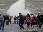 Erneute Eskalation: Palästinensische Demonstranten fliehen am Samstag vor Tränengas der israelischen Sicherheitskräfte. (Bild: KEYSTONE/EPA/ALAA BADARNEH)
