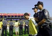 Chinesische Polizisten halten im Stadion in Shuangliu einen verurteilten Drogenhändler fest. (Bild: AFP)