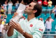 Roger Federer liebkost seinen Preis nachdem er den US-Amerikaner John Isner besiegt hat. (Bild: EPA/RHONA WISE, Florida, 31. März 2019)