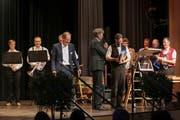 EKS-Geschäftsführer Dani Müller überreicht Philipp Langenegger als Dank für die gelungene Moderation des Jubiläumsanlasses einen Käse. Links Roger Greutmann, Präsident des EKS-Stiftungsrates. Bild: Leo Graf