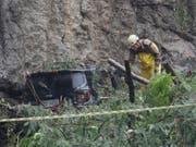 Ein Rettungsarbeiter sucht im Schlamm und unter umgestürzten Bäumen nach möglichen Opfern. (Bild: KEYSTONE/AP/SILVIA IZQUIERDO)