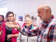 Fotograf Adrian Scherrer erklärte den Besucherinnen und Besuchern ausführlich Details zu den Bilderpaaren. (Bild: Sascha Erni)