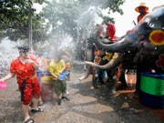 Nasse Neujahrsgrüsse vom Dickhäuter: Elefanten besprühen Passanten an Songkran in Ayutthaya, Thailand. (Bild: KEYSTONE/EPA/RUNGROJ YONGRIT)