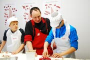Zwei Kinder lernen von Fleischfachmann Reto Rust (Mitte), wie ein Schwägalpspiessli entsteht. (Bild: Michael Hehli)