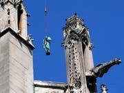 Die Paulus-Statue wird vom Turm der Kathedrale Notre-Dame auf den Boden geholt. Die Statuen der zwölf Apostel und der vier Evangelisten müssen restauriert werden und sind deshalb erstmals seit über hundert Jahren aus der Nähe zu betrachten. (Bild: KEYSTONE/AP/FRANCOIS MORI)