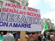 «Wir haben Euch satt - haut ab» steht, an die Machthaber gerichtet, auf einem Schild, das Protestierende an der Freitagsdemonstration in der algerischen Hauptstadt mit sich führen (Bild: KEYSTONE/AP/FATEH GUIDOUM)