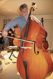 Francisco Obieta greift zu einem der vier Kontrabasse in seiner Stube in Au, um ein Stück zu spielen. (Bild: hb)